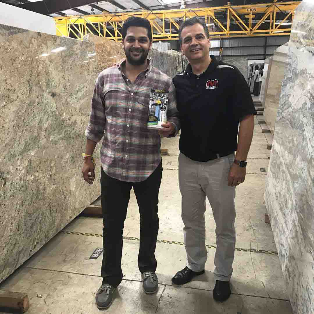 Pictured is founder of Supreme Surface, Tom Munro, and one of his first distributors in Tampa Florida, Elegant Marble & Granite. They are standing in front of granite slabs holding a bottle of Supreme Surface All-In_one: Granite and Quartz sealer, polish and cleaner.